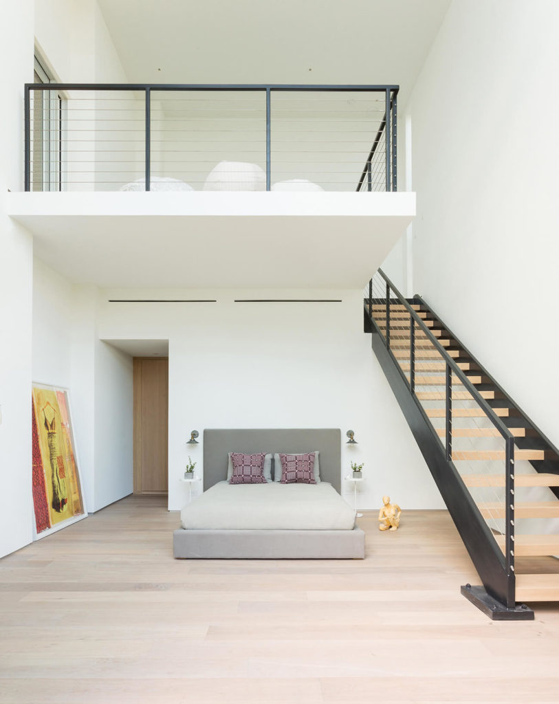 Spacious master bedroom boasts a private loft area lined with an open riser staircase. Beneath it is the gray bed surrounded with art decor figurines.