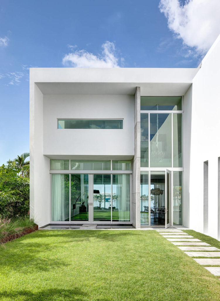 Viewed from the central courtyard, we can see right through the home toward the bay, courtesy of extensive glasswork and clear, open-plan design.