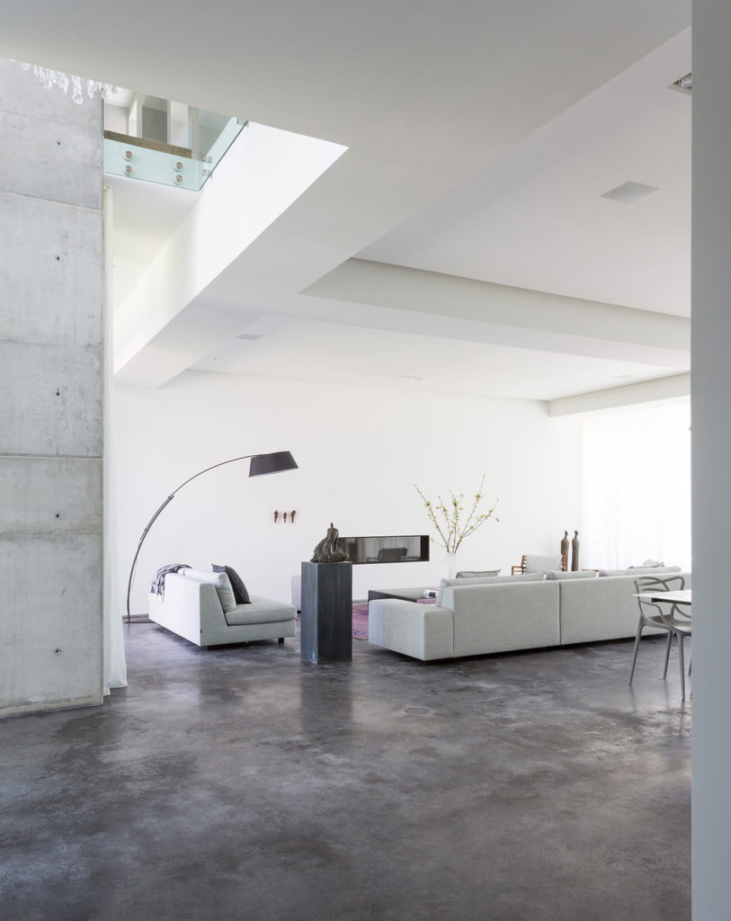 The grand, open-plan living room features a set of light grey contemporary sectionals over an expanse of dark stone flooring, contrasting with bright white surroundings. The upper floor can be seen peeking over at top left.