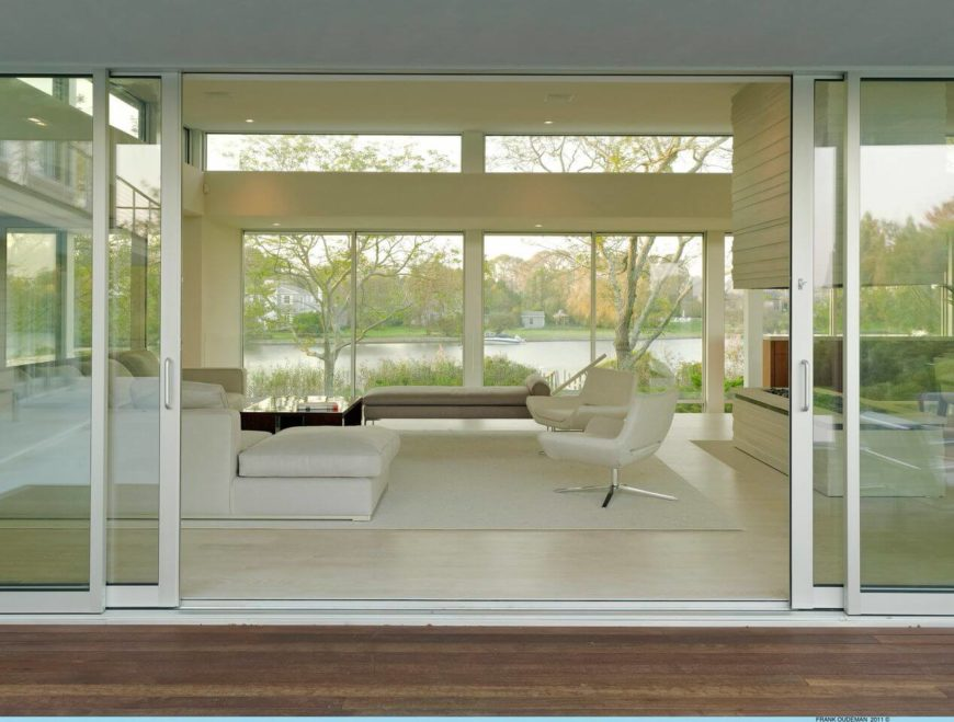 Another look through the living room shows the pond on the north side of the home. The enormous seamless windows provide the main living spaces with fantastic views of the water.