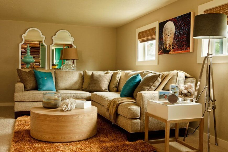 The downstairs sectional has a round oak coffee table on a plush orange-red area rug.