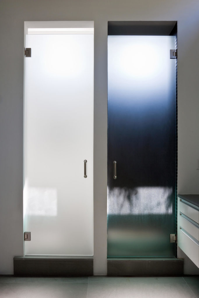 Doors to water closet and shower features two contrasting tones of smoked glass, a unique addition to an already striking bathroom.