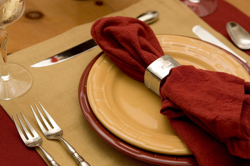 Dining table place setting in red and beige.