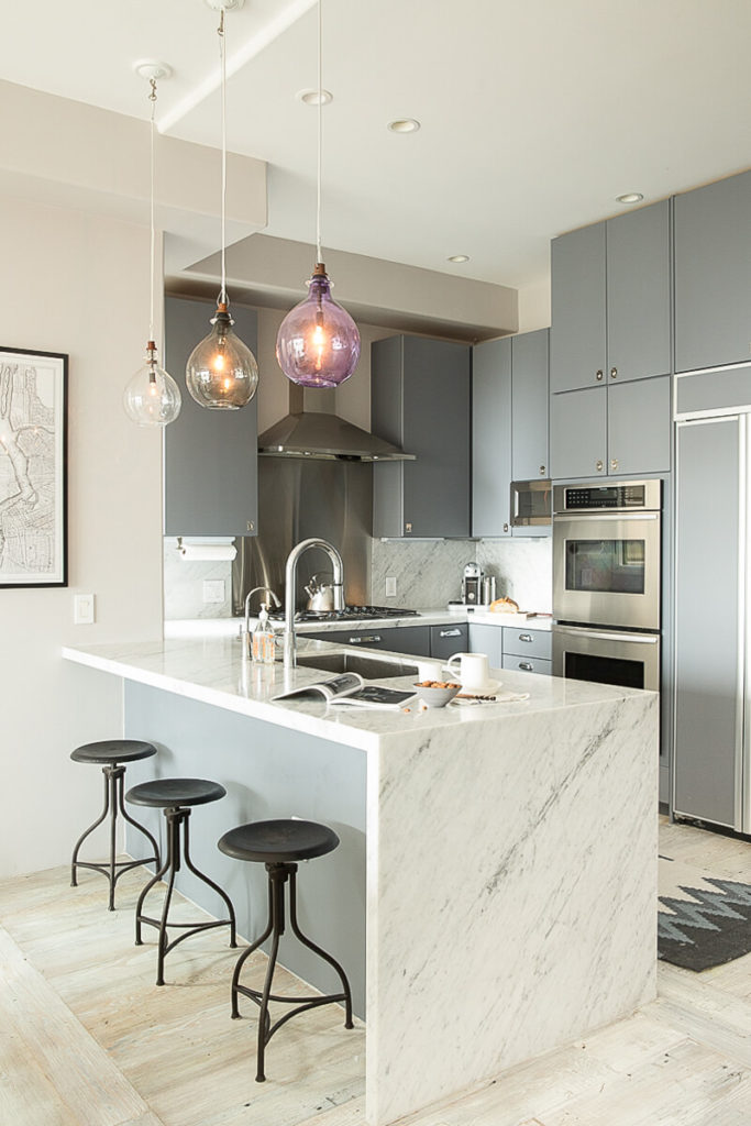 The kitchen transitions from the modern minimalism of the living room and dining room into a more contemporary-modern aesthetic. The kitchen island is in white granite that extends to the light wood flooring.
