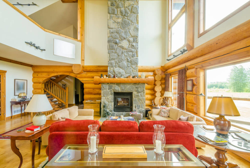 A Modernized Log Cabin With An Enormous Stone Fireplace. The Wooden Mantle  Is Wider Than