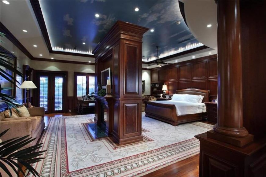 An absolutely stunning master bedroom in polished hardwood. A center fireplace is dual-sided and can be enjoyed from the bed or from the sofa on the left.