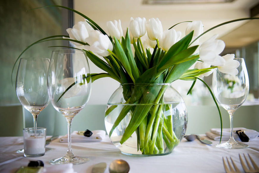 A white tablecloth with simple folded napkins and delicate wine goblets. At the center of the table is a large globe vase with white tulips.