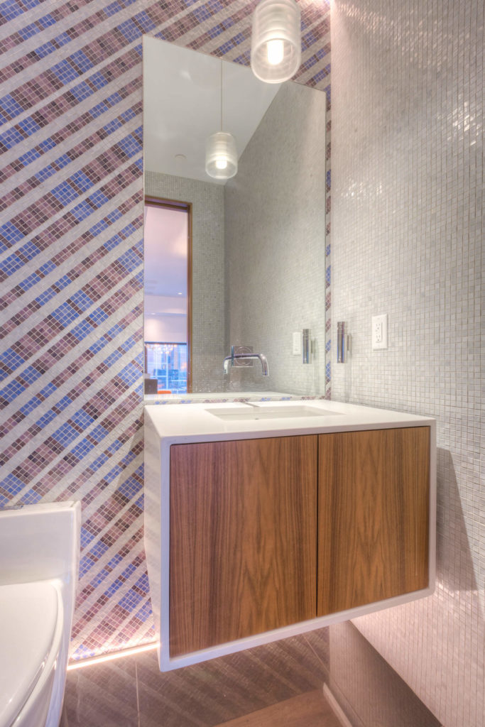 This bathroom is defined by a dazzling micro-tile wall in soft blue and red, with a floating white vanity housing natural wood cabinet doors.