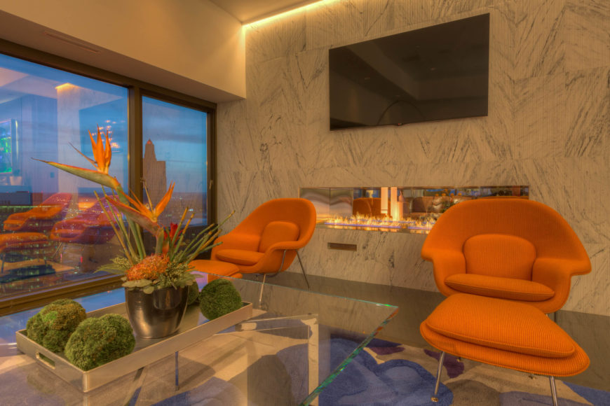 Here we have a close view at the living room corner, embraced by a massive marble wall with gas fireplace embedded at center. The bright orange chairs stand out from the stately tone of the room, abetted by a matching burst of birds-of-paradise on the coffee table.