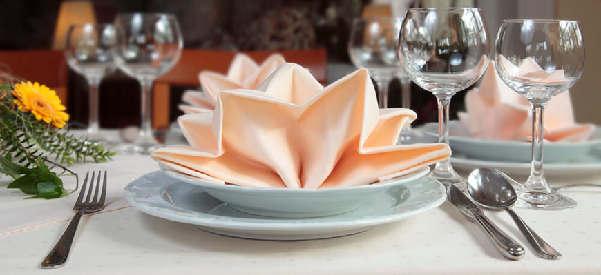 A contemporary table setting with scallop-rim dishes and peach napkins folded artfully and placed : table napkin setting - pezcame.com