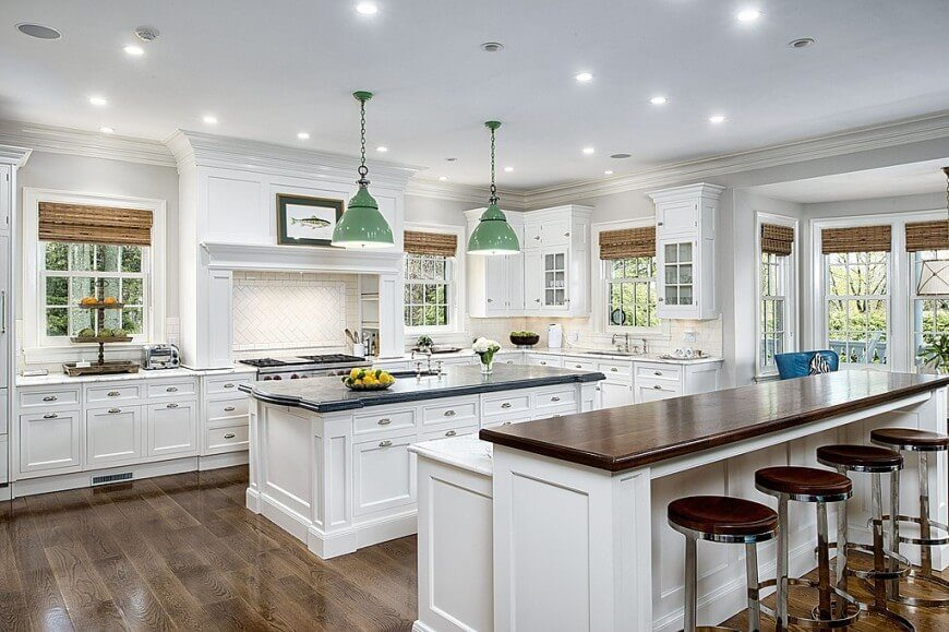 These great english styled windows in this fantastic kitchen are paired with bamboo woven shades. The shades are a great partner to the dark wood on the bar and hardwood flooring.
