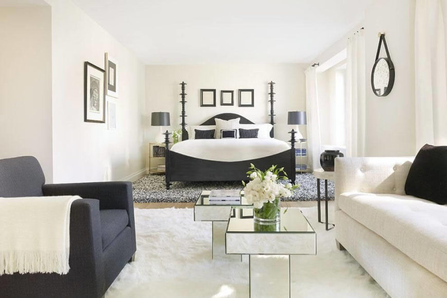A bright white bedroom with charcoal gray accents and a plush rug beneath the bed. A white tufted sofa sits across from a gray armchair with two mirrored side tables in the center.