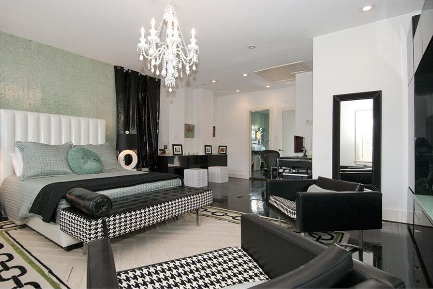A contemporary primary bedroom with deep loveseats in black faux leather and houndstooth fabric. The wall behind the bed is in shimmering seagreen mosaic tile.