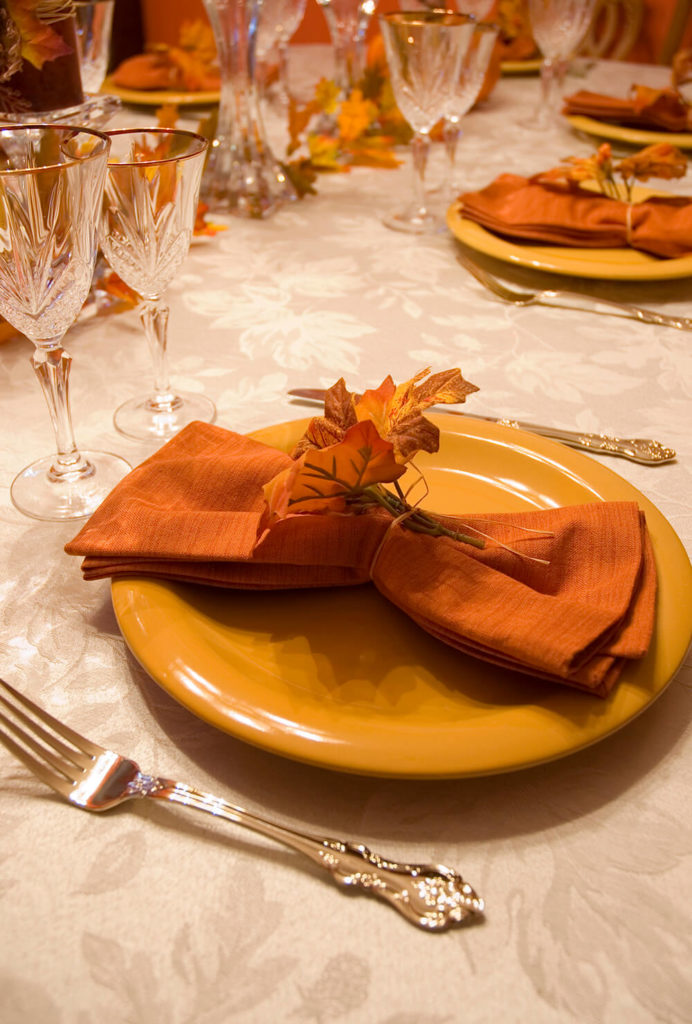 A table setting that would be perfect for a family Thanksgiving in gold-yellow and rust-orange. Napkin rings are fashioned from fake autumn leaves secured with twine. Even the wine glasses have a subtle leaf motif.