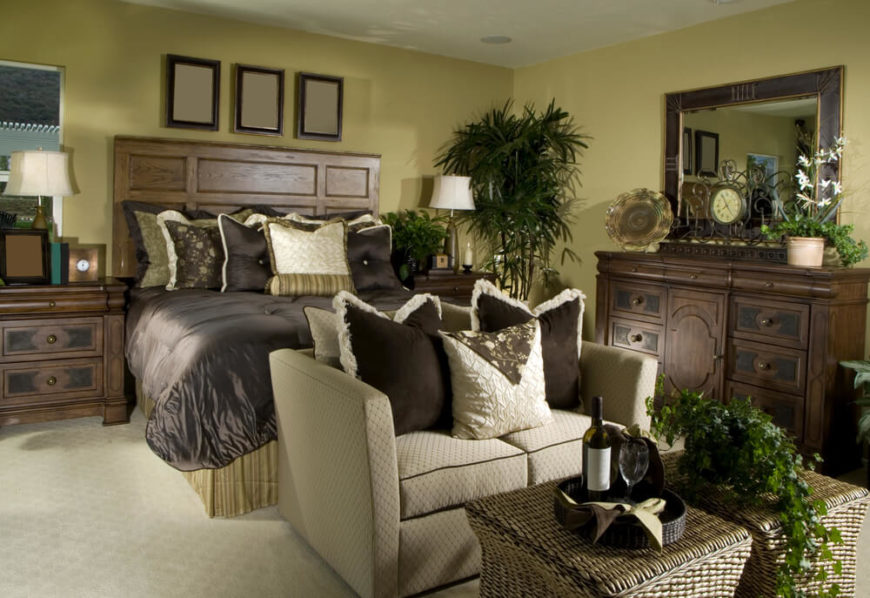 A smaller master bedroom with a beige loveseat at the foot of the bed. A wicker coffee table holds a small tray with wine and wine glasses.