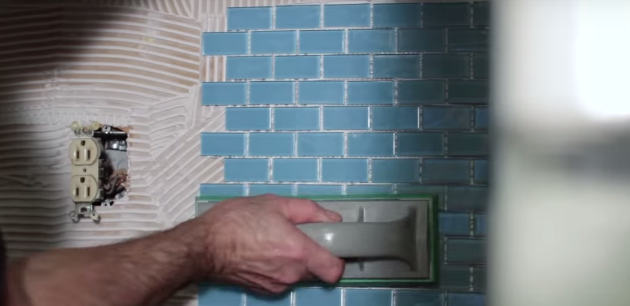 "Use your rubber float to ""tamp"" the tile into the adhesive securely and evenly."