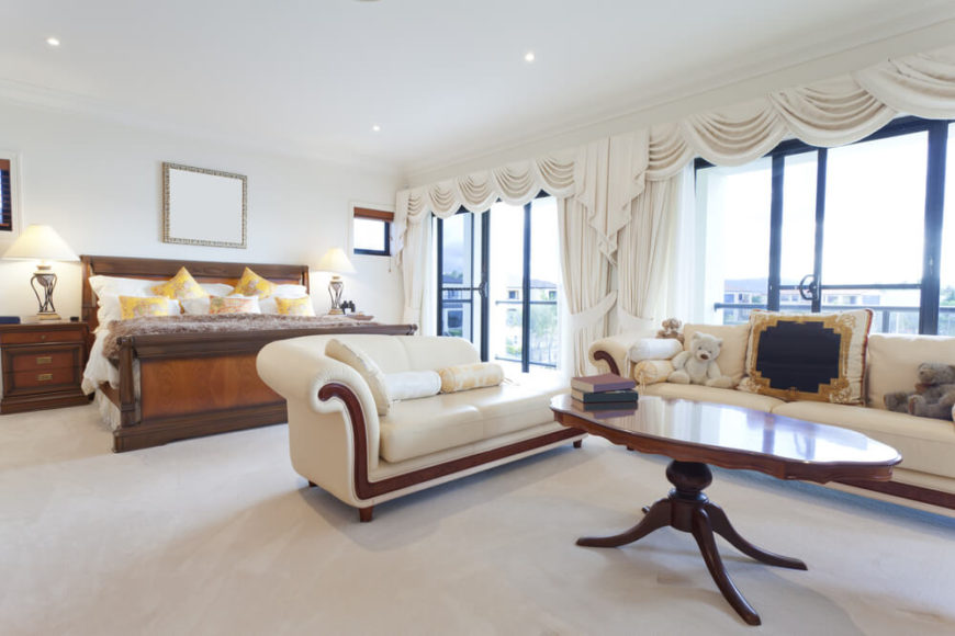 A light and bright master bedroom with a large sofa and chaise lounge in cream with polished hardwood accents that match the tall table between the two. Sliding glass doors lead out onto a terrace.