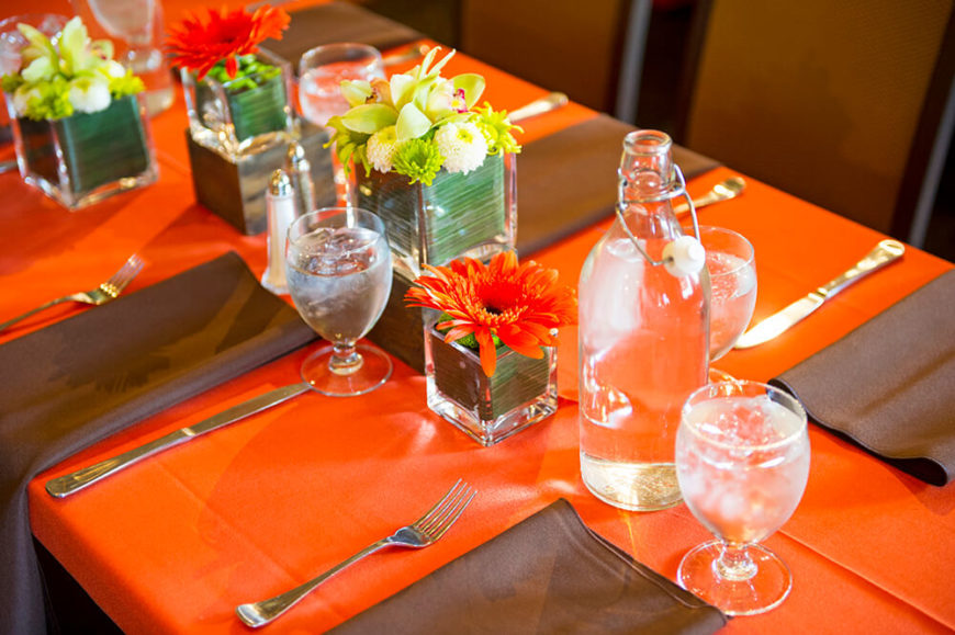 A bold orange and brown table setting with small floral arrangements. This setting is for a kitchen-served dinner, as there are no plates on the table.
