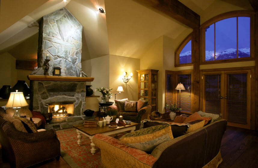 A cavernous traditional living room with a free-standing all-stone fireplace. This chalet overlooks the mountains and the shaded doors lead out onto a large terrace.