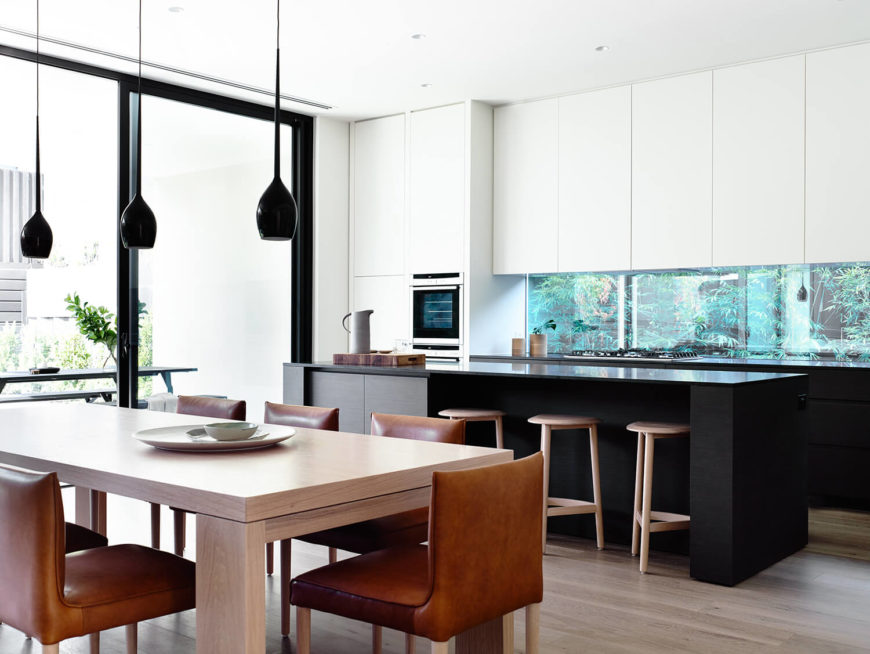 The main living area of the home is open-concept. This view focuses on the dining room and the minimalist kitchen in white and black. Perhaps the most stunning feature of the kitchen is the terrarium visible through the glass panels beneath the wall cabinets--a creative way to merge synthetic minimalism with an organic element.