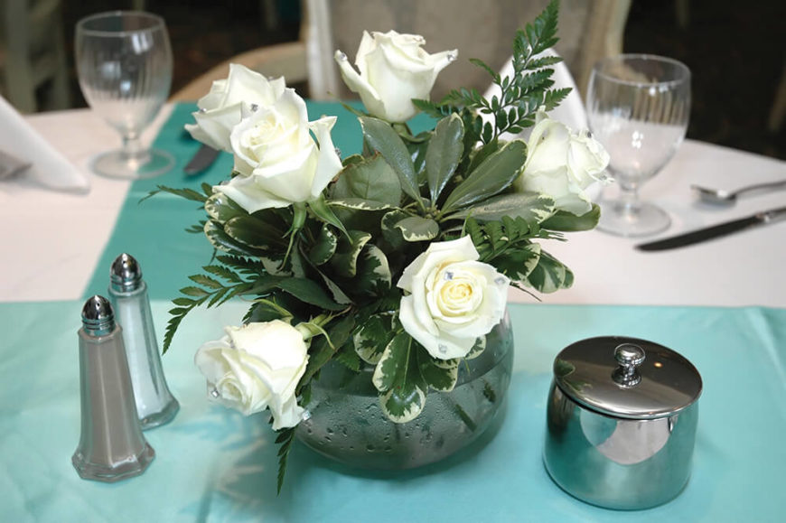 A Small And Delicate Floral Arrangement Consisting Of White Roses Tucked  Into A Glass Vase With