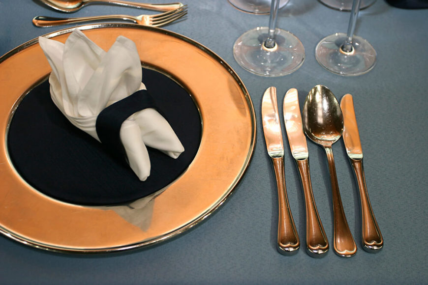A formal place setting with a gold-rimmed plate and utensils to the right of the plate. Dessert utensils are above the plate, next to the wine glasses.