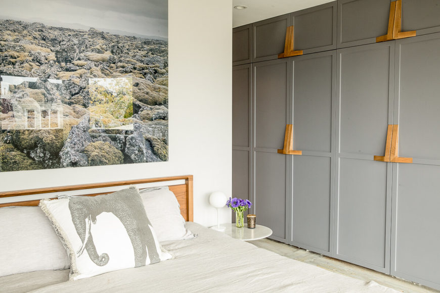 The only clue to how the storage cabinets open are the wooden handles scattered through the panels. An enormous panoramic shot of a rocky landscape is displayed above the bed.