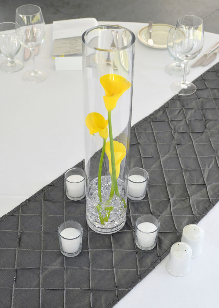 A tall glass vase with crystals and a bit of water at the bottom is filled with three yellow calla lilies ranging from short to tall.