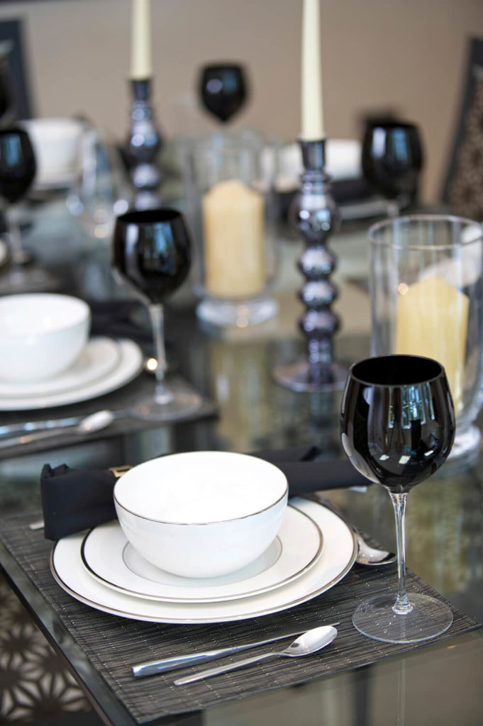 A gray and white table setting with accents of black. While the napkin is a more muted, dusky black, the top of the wine glass is a solid, glossy black inside and outside for a stunning effect.