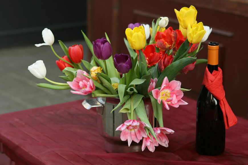 A beautiful springtime floral arrangement in an old steel dutch oven filled with tulips in yellow, pink, purple, red, and white.