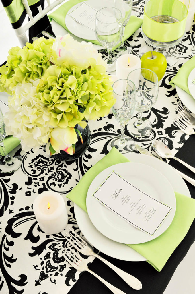 A contemporary damask black and white table cloth with white pillar candles for ambient lighting and a light green napkin between the dinner plate and the salad plate. A simple menu sits at the center of the arrangement.