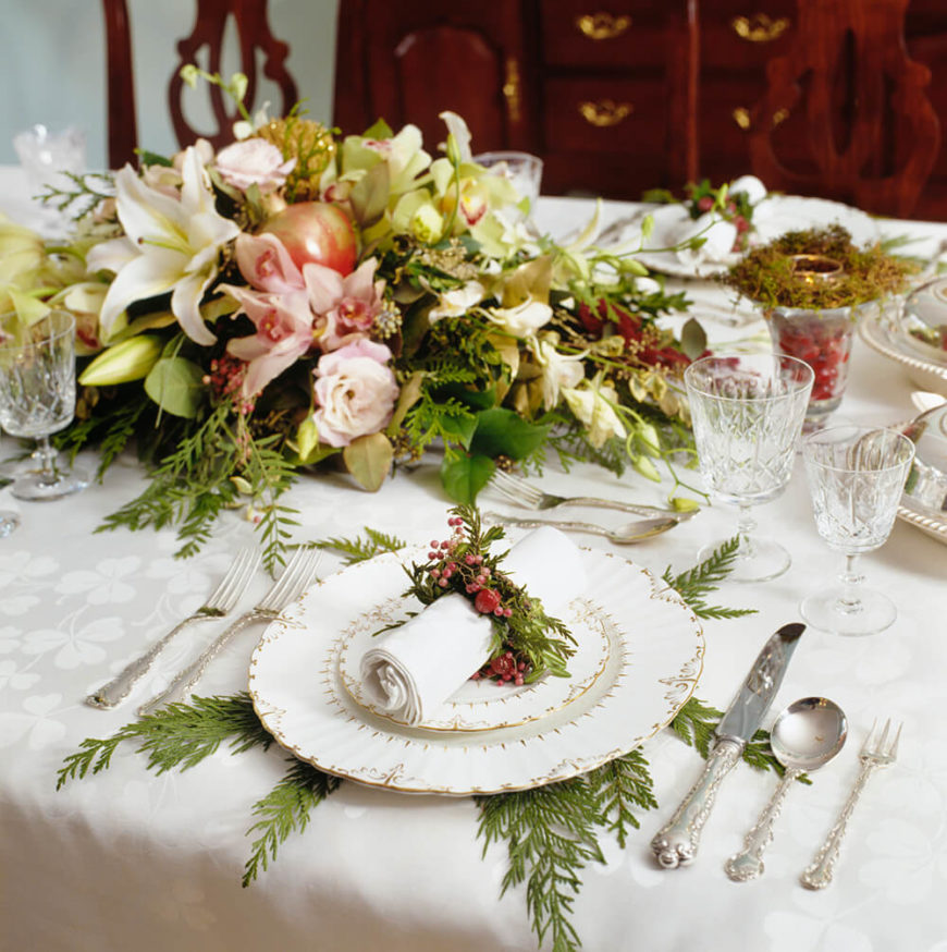 This low-profile centerpiece combines roses and lilies with evergreen boughs and an apple to create a centerpiece perfect for Christmas dinner.