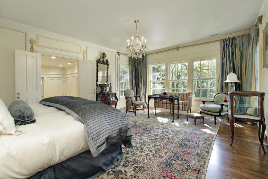 An ornate master bedroom suite with a traditionally patterned rug and a large seating area near the windowed rear of the room. The seating area consists of a tall coffee table, two armchairs, and a striped loveseat.