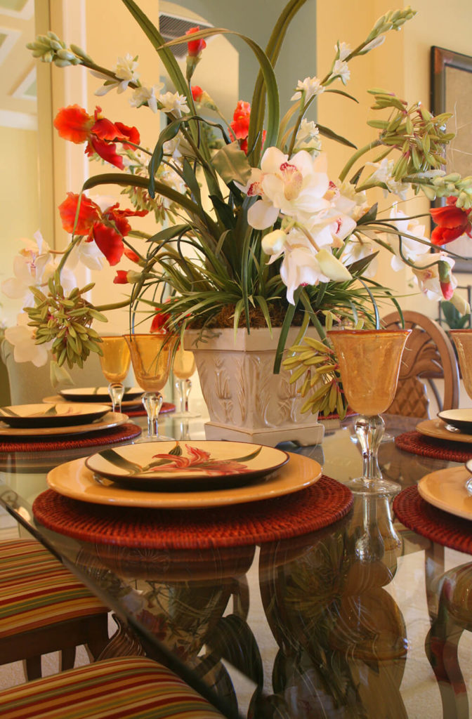 A Large Grouping Of Orchids And Other Tropical Flowers Spill Over This  Glass Topped Table
