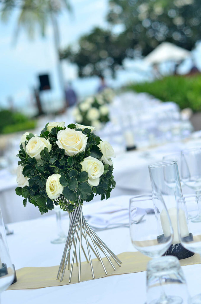 A beautiful and elegant wedding centerpiece consisting of short-stemmed roses and greenery tucked onto the top of a modern silver holder.