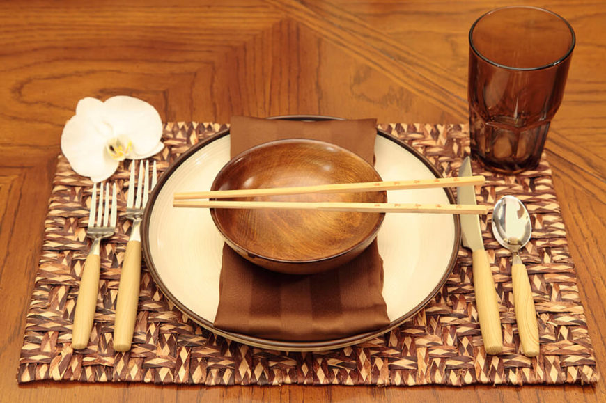 An Asian inspired table setting on a natural fiber place mat. A white orchid bloom sits on the top left corner, and a pair of chopsticks lays across the bowl, in addition to the western utensils on the side.