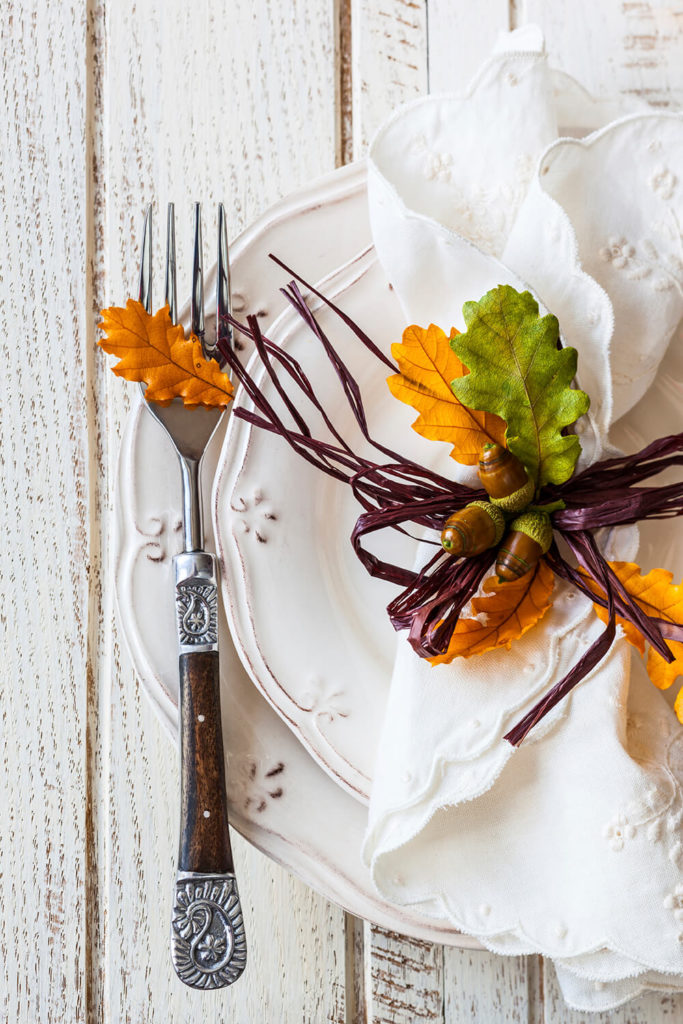 An autumn table setting on vintage dishes on a distressed white table, minus any linens.