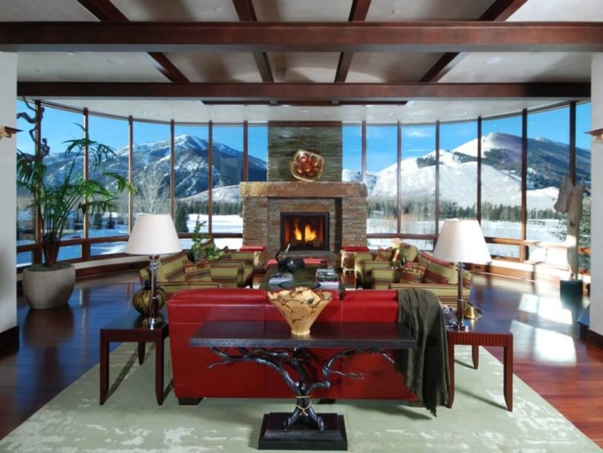 A window-wrapped great room with an enormous stone fireplace at the very center. Even the huge mantle is solid stone, making this fireplace unbelievably heavy. The fireplace is the perfect complement to the snowy mountainside view.