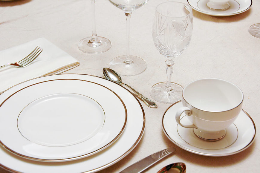 A Simple But Elegant Table Setting In White With Silver Rimmed Dishes. Each  Wine