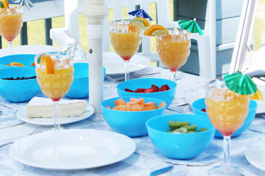Bright blue plastic serving bowls full of fruit combined with glassware that resembles a pineapple makes for an excellent tropical themed summer dinner party.