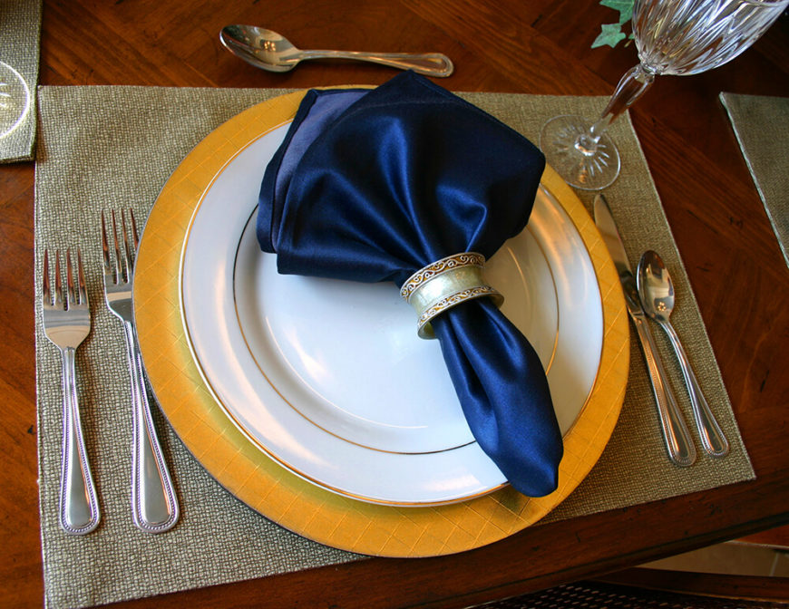 A more simple gold, white, and blue place setting on a gray woven place mat.