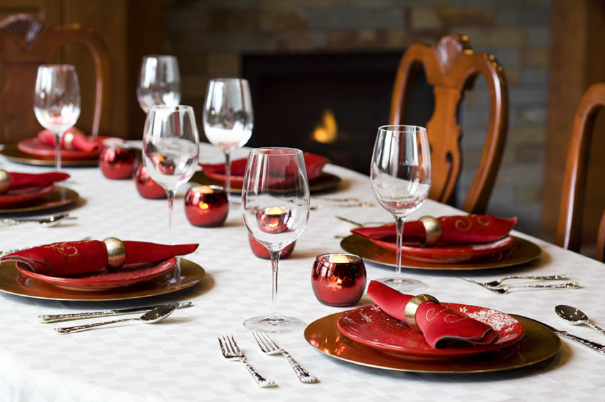 A festive holiday table setting with rid dishes with a subtle snowflake pattern on top of gold dinner plates. A line of red candle holders act as the only centerpiece.