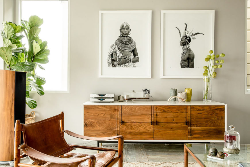 Here we have a closer look at a white and wood entertainment center topped by various pottery, antlers, technology, and by two gorgeous portraits of African tribesmen. Vases of flowers and tall potted plants add a sense of the organic to this white, minimalist room.