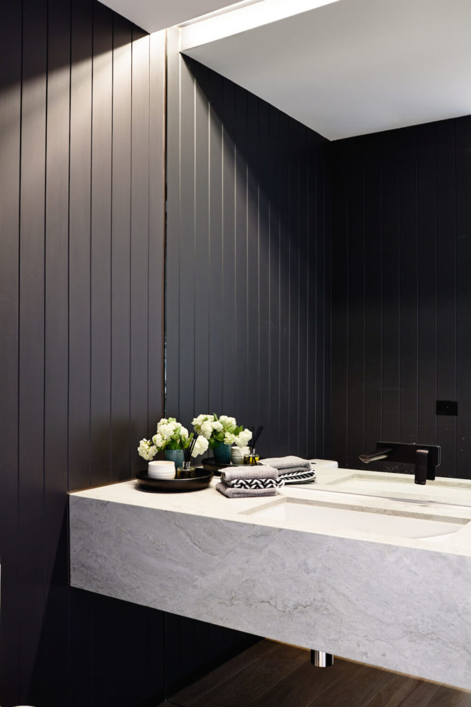 As one of the home's two powder rooms, this bathroom features dark-stained wood panelling and a white granite floating countertop. High end contemporary fixtures add additional luxury.