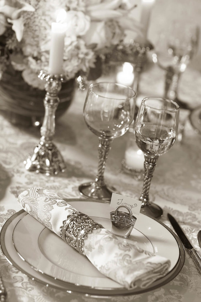 A beautiful wedding table setting in silver and white with ornate wine glasses and damask patterned linens. A small silver purse acts as a place card.