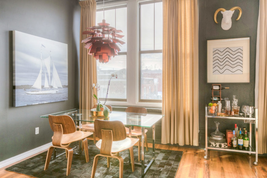 The cream toned drapes and immense windows grant a brightness to the space that allows the dark painted walls to contrast, without darkening the space. A small retro chrome drink stand is placed at right, below wall mounted artwork.