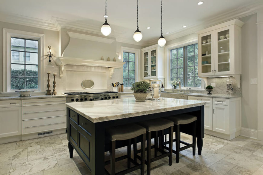 This striking kitchen brings together both rustic and contemporary themes. This space has an old fashion vent hood and rustic hanging lights to complete a unique design. Colonial styled windows bring in the classic atmosphere to this elegant kitchen.