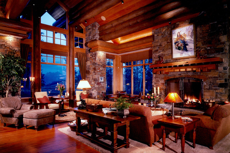 An enormous log-cabin style chateau in the mountains with a massive screened wood-burning fireplace in stone. The mantle is carved natural wood in the same color as all of the beams.