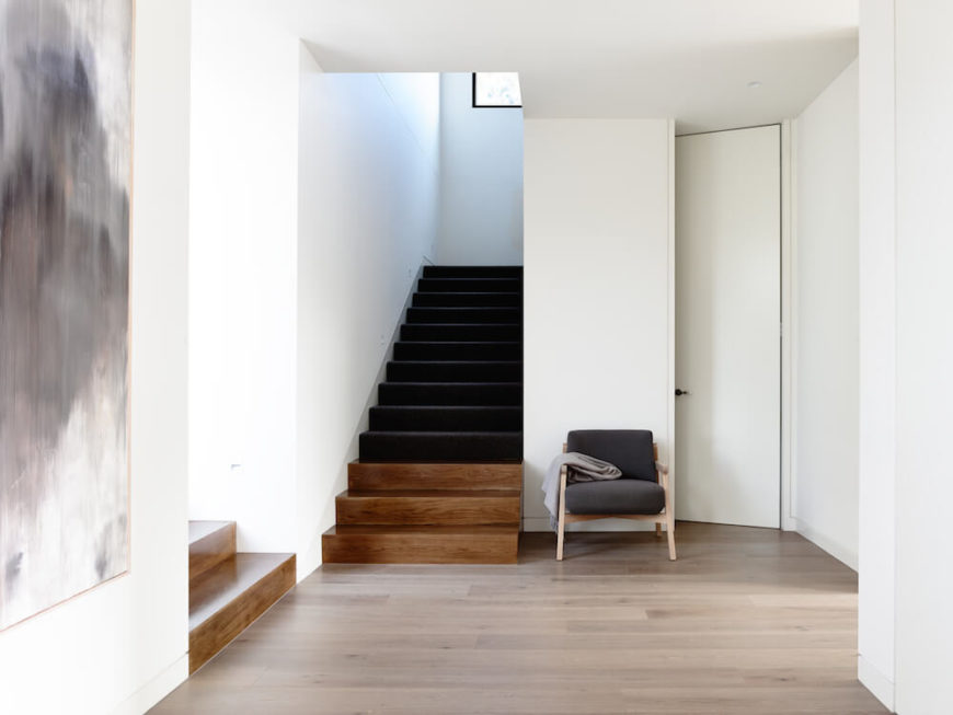 As we return to the beginning of the home, we see a landing between the foyer and the staircase leading to the second floor. To the right is a small closet.