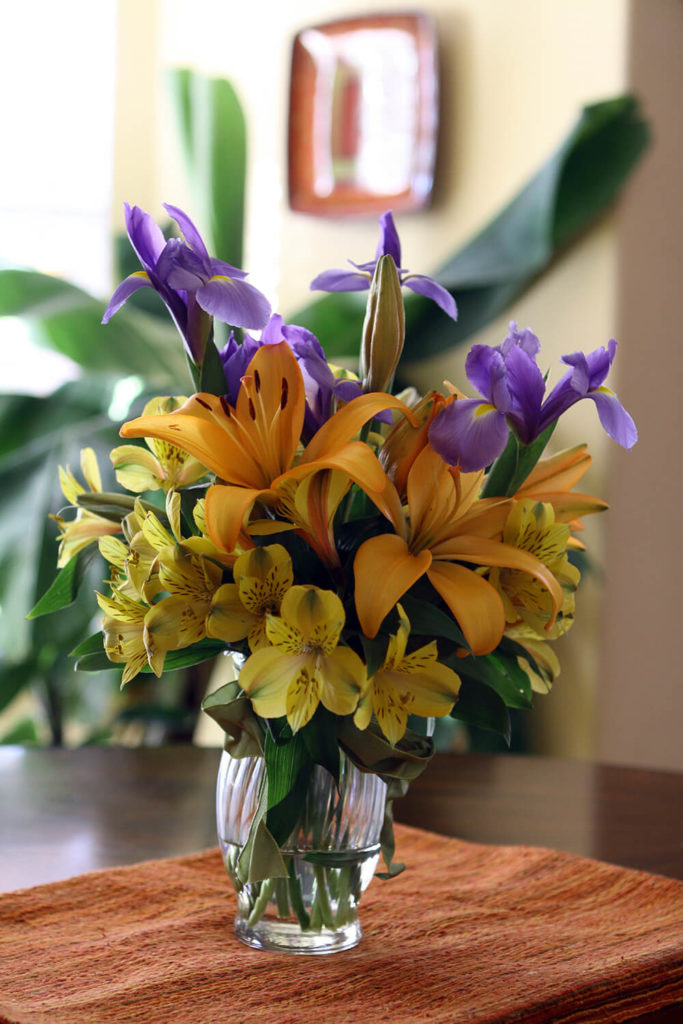 A beautiful full bouquet of lilies and irises in a ridged glass vase is a summery addition to any table and adds a pop of color to the room, in addition to a haunting scent.